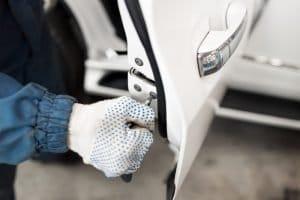 Automotive locksmith repairs car door lock