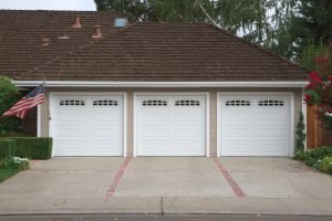 Beige three car garage with white doors and brick and red brick driveway