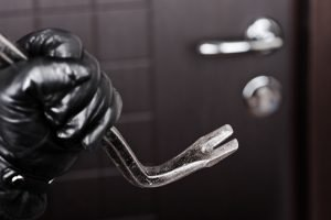 Burglar hand in gloves holding metal crowbar