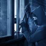 Burglar using crowbar to break into a house at night