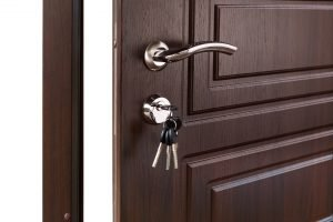 Open door handle. Door lock with keys. Brown wooden door with modern interior design, door handle.