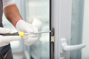 locksmith holding a screwdriver and fixing the lock of commercial door