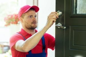 Locksmith performing house door lock maintenance