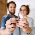 Young married couple moving into a new house, holding a key together.
